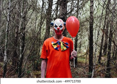 a scary evil clown wearing a dirty costume, holding a red balloon in his hand, in the woods