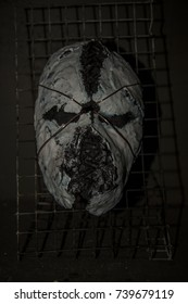 Scary evil mask hanging on the wall in an abandoned house. Mask for dark ritual.