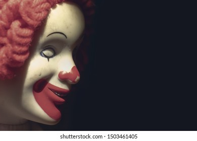 Scary evil sinister clown face with a spooky smile on black background with copy space, coulrophobia and fears concept.