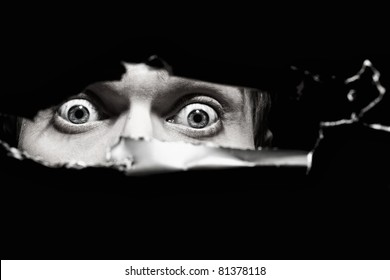 Scary eyes of a man spying through a hole in the wall close up