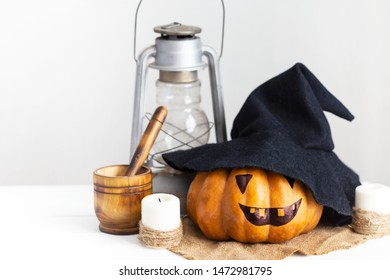 scary face pumpkin, witch hat, candles and lantern on a white wooden table. Autumn Halloween concept. Rustic style Copy space
