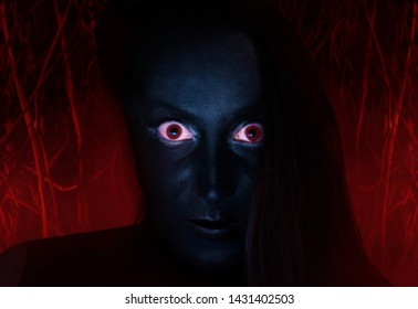 Scary face of a witch with dark skin and red eyes staring, with burning wood background, close-up.