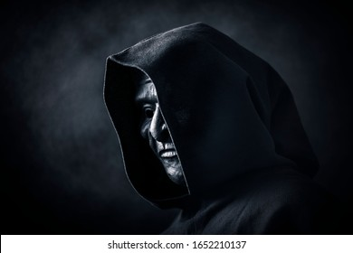 Scary figure in hooded cloak with mask