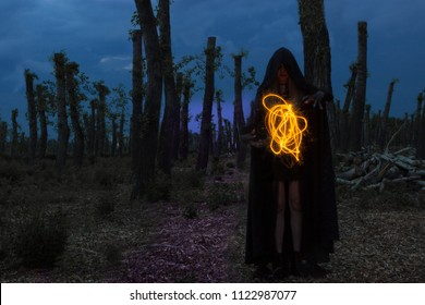 Scary Halloween concept: a witch in a black Cape conjures up in a dark night forest. multi exposure