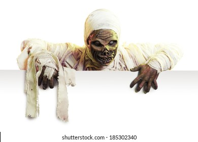 Scary Halloween mummy holding a sign isolated on white