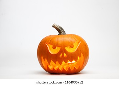 Scary Halloween pumpkin head jack lantern with burning candles isolated on white background