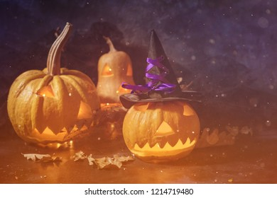 Scary Halloween pumpkin on a black background. Scary glowing face trick or treat with autumn leaves