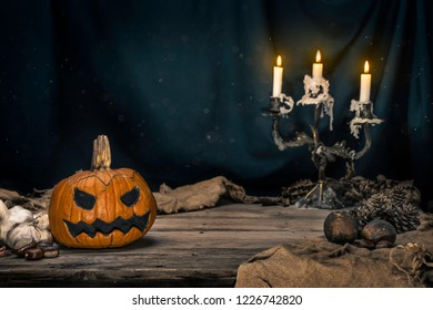 Scary halloween pumpking. Dark background with colorful lights. Helloween theme. Scary postcard. Horror face. Card invitation. Lantern with burning candles, still life. Autumn Spooky, evil, celebratio