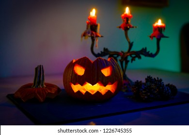 Scary halloween pumpking. Dark background with colorful lights. Helloween theme. Scary postcard. Horror face. Card invitation. Lantern with burning candles, still life. Spooky, evil, celebration