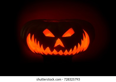 Scary Halloween pumpkins with eyes glowing inside at black background
