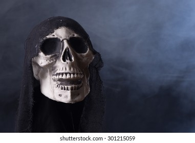 Scary Halloween skull on a black smoky background with copy space