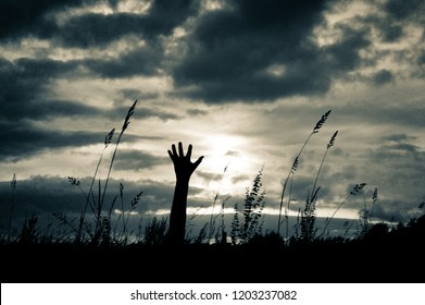 A scary hand silhouetted against the sun with a grunge, vintage duo tone edit