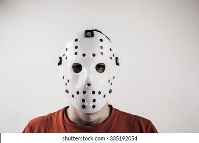 Scary hockey white mask on young man isolated on white background. Close up portrait.