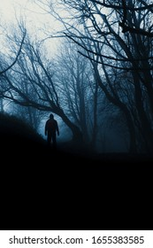 A scary, hooded figure standing in an eerie, spooky forest. On a misty evening.