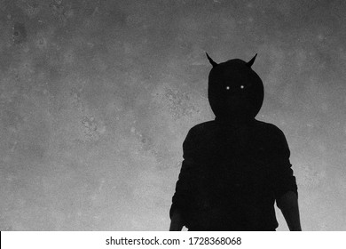 A scary, hooded horned figure with glowing evil eyes looking down to camera. With a grainy textured edit