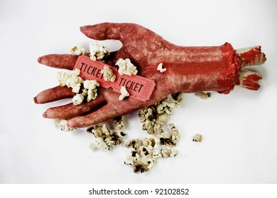 Scary Image Of A Bloodied Dismembered Hand Holding Popcorn And Tickets To The Movies In A B-Grade Horror Film Review Concept