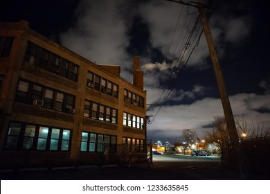 Scary industrial urban street city night scene with a vintage factory warehouse and smokestacks