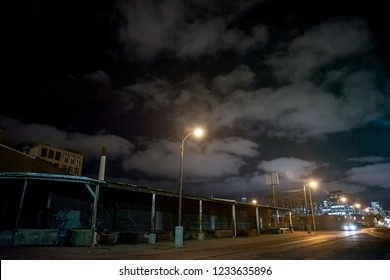 Scary industrial urban street city night scene with train tracks and loading docks by vintage factory warehouses