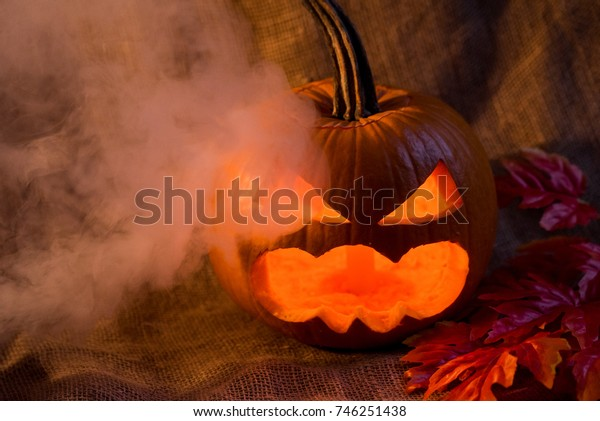 Scary jack-o-lantern, light inside and red leaves