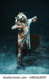 Scary little zombie girl standing on the bed next to a bloody axe. Halloween. Horror movie.