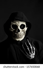 A scary looking hooded Skeleton beckoning you over, dark background.