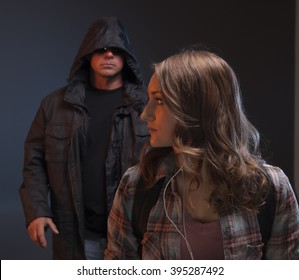 Scary man is about to grab a girl.  Teenage Girl gets attacked by a stranger.