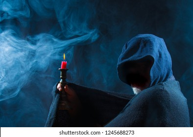 a scary man holds a candle in his hand