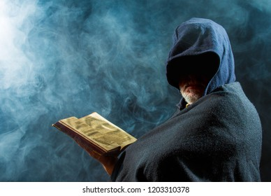 a scary man is reading in an old book