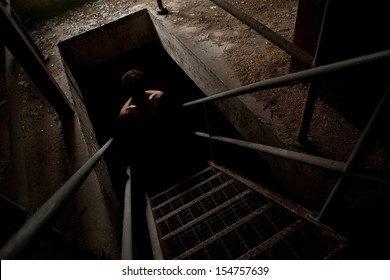 Scary man silhouette in the dark staircase with light only on the shoulders