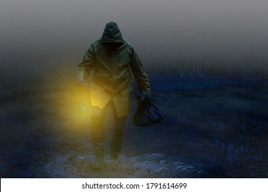 A scary man with wading boots , rain jacket and a bag wades by candlelight through the foggy swamp.