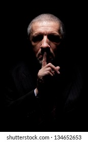 Scary mature man gesturing silence. Black background