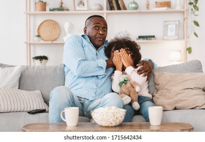 Scary movie night. Mature African American man with his little granddaughter closing face in horror at home