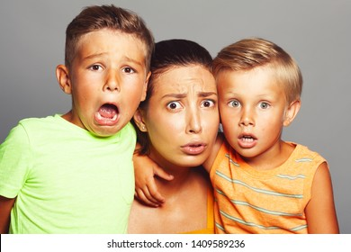 Scary movies, Oh, my God concept. Portrait of frightened into fits fashionable baby boys and their stylish mother in trendy summer clothing looking at camera. Close up. Studio shot