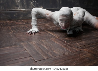 Scary mummy creeps on you. The girl with the bandage Crawling on the floor. Halloween costume