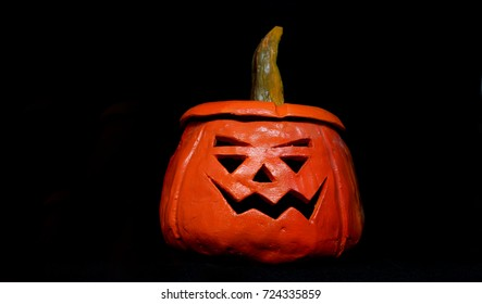 Scary orange pumpkin on a black background on a Halloween holiday