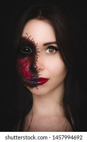 Scary portrait of a woman with black eye and a cursed mark on her face on dark background. Demonic nature in an innocent body