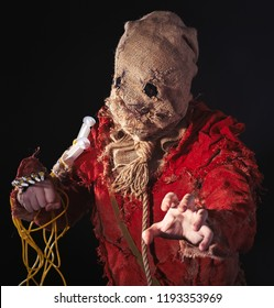 Scary Scarecrow character in a sackcloth suit with syringes on dark background. Cosplay hero