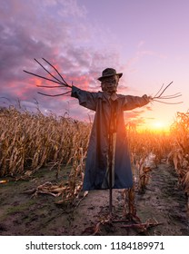 Scary scarecrow in a hat on a cornfield in orange sunset background. Halloween holiday concept