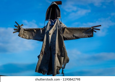 scary scarecrow hooded against the blue sky
