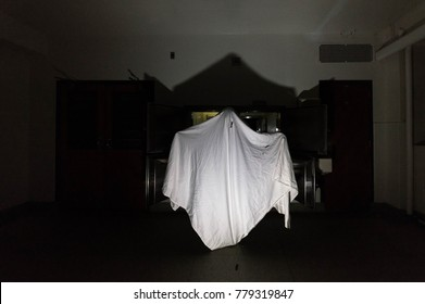 A scary sheet ghost in the morgue of an abandoned mental hospital