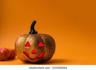 Scary shiny Halloween pumpkin toy. Jack-o'-lantern on an orange background with red luminous eyes with a place for text.