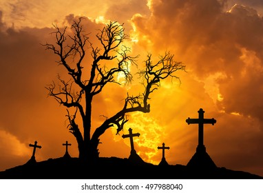 scary silhouette dead tree and spooky silhouette crosses in mystic graveyard in Halloween concept background