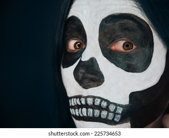 Scary skull woman looks at camera, Halloween makeup