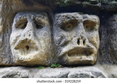 Scary Stone Heads - rock sculptures of giant heads carved into the sandstone cliffs, Czech republic