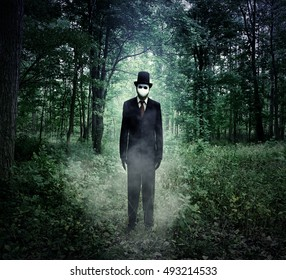 A scary tall man in a black suit is standing in the dark woods at night with fog for an evil Halloween or fear concept.