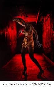 Scary undead zombie woman in the dark corridor. Halloween theme.