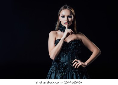 scary vampire girl in black gothic dress showing shh sign isolated on black