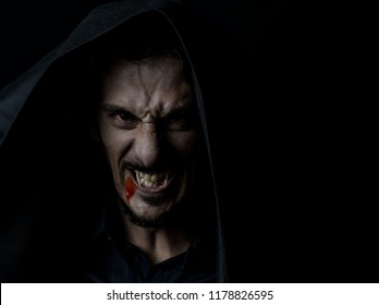 Scary Vampire in the hood with Red eyes and blood on the mouth