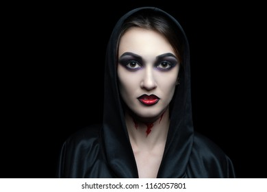 Scary vampire make-up for Halloween. Cut skin on throat, blood flowing from wounds. Black shadows smoky eyes. Horrors of terrible nightmares. Large hood cape woman vamp. Horizontal banner concept idea