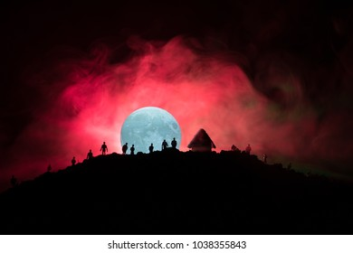 Scary view crowd of zombies on hill with spooky cloudy sky with fog and rising full moon. Silhouette group of zombie walking under full moon. Halloween concept.